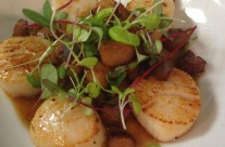 Seared scallops and pork belly with caramelized onions